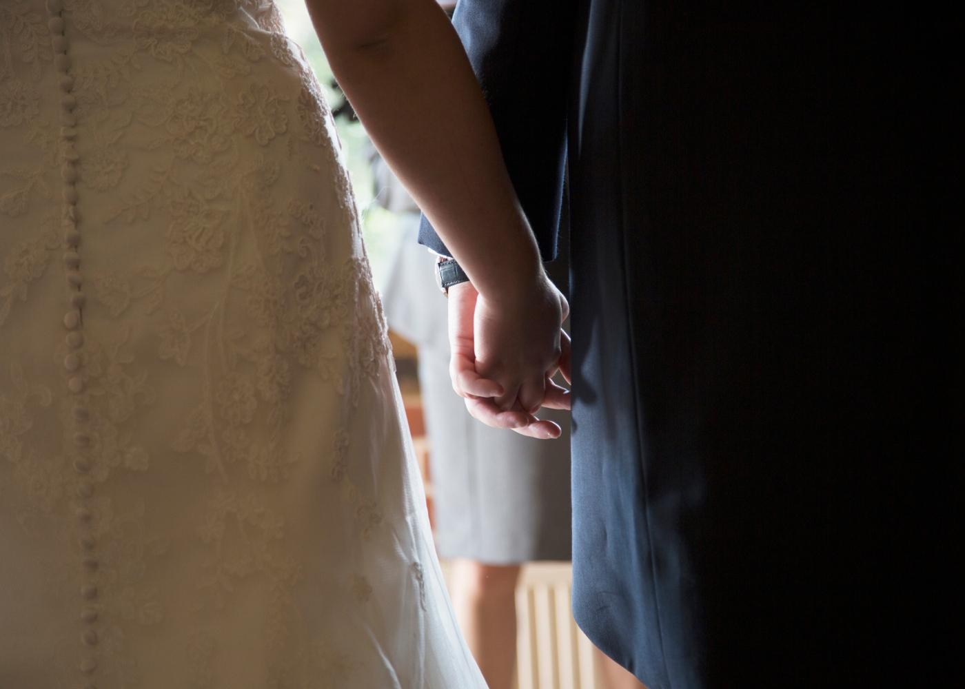casal de mão dada a sair da igreja