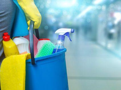pessoa a segurar balde com produtos de limpeza