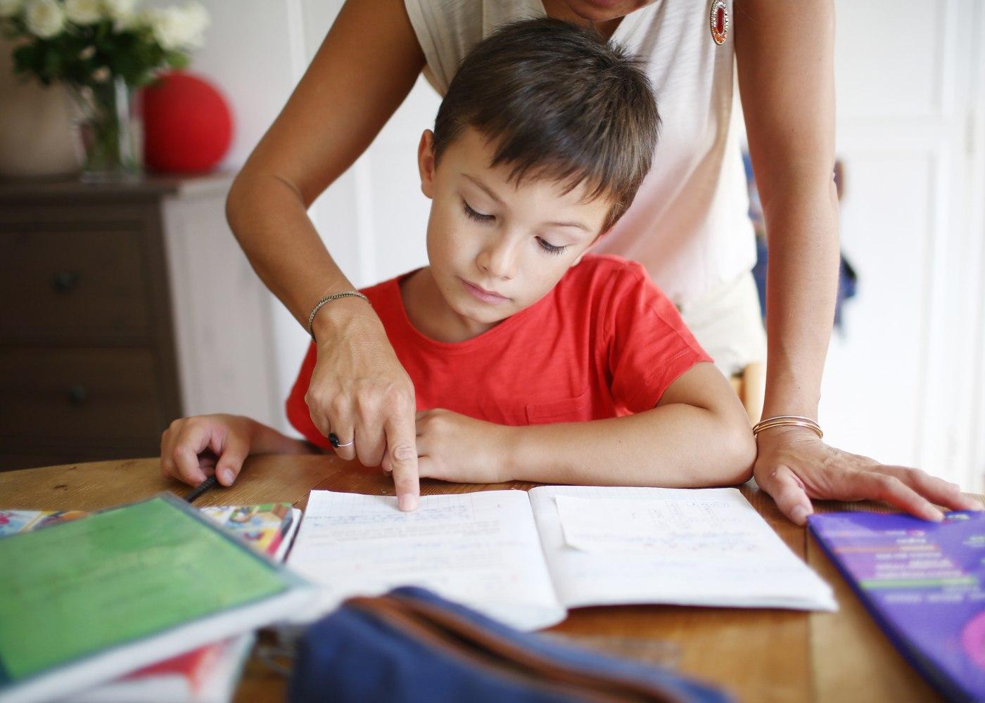 mãe a ajudar filho nos trabalhos da escola