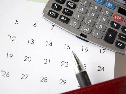 calculadora, caneta e calendário em cima de uma mesa para analisar situação de salários em atraso