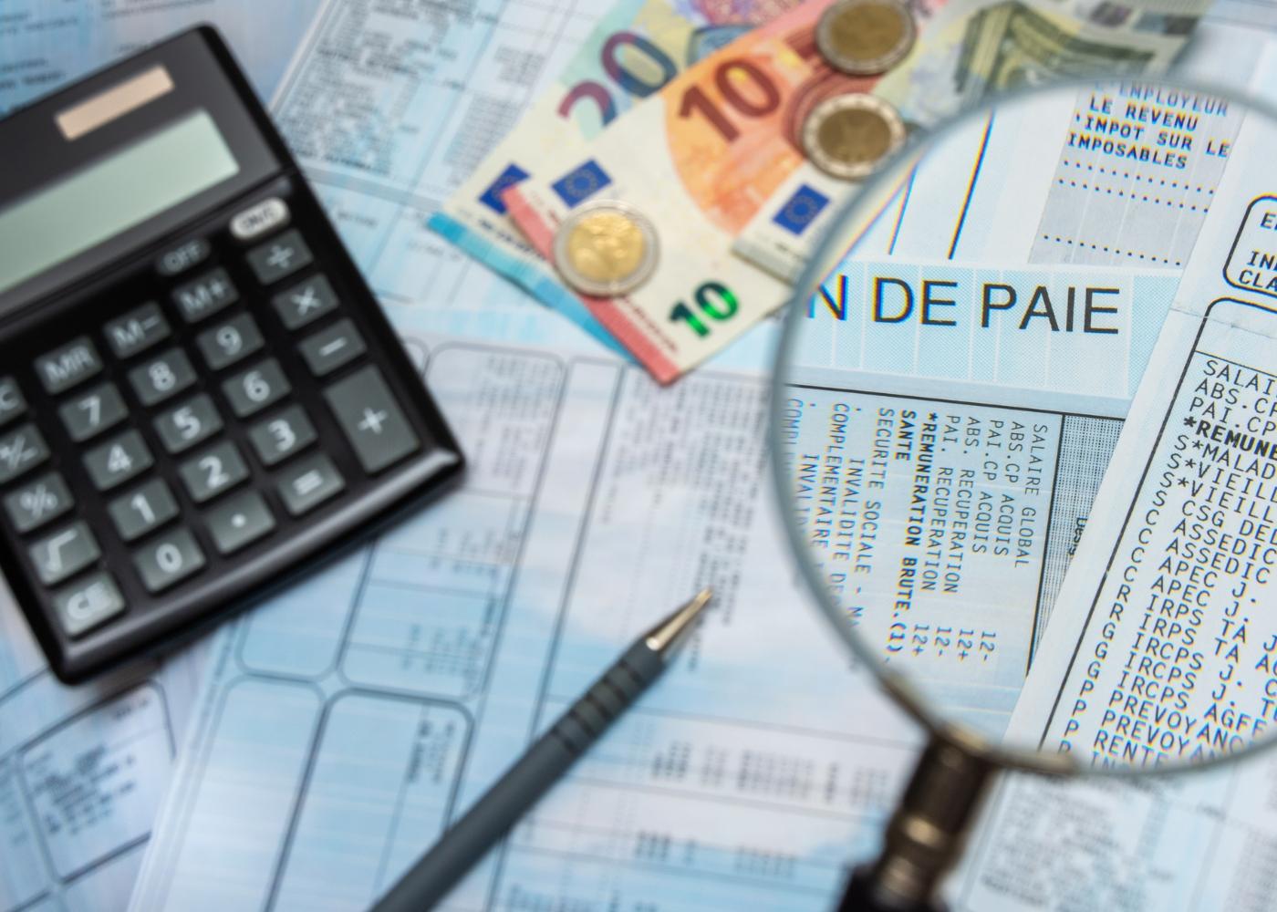 calculadora, dinheiro e formulários do subsídio de desemprego