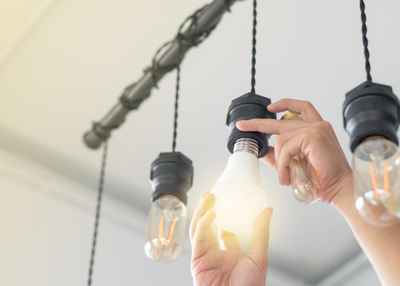 Mulher a substituir lâmpadas incandescentes por lâmpadas LED