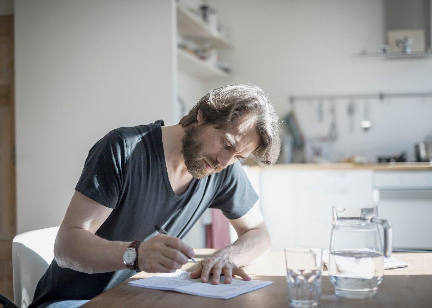 homem em casa a assinar um contrato de prestação de serviços