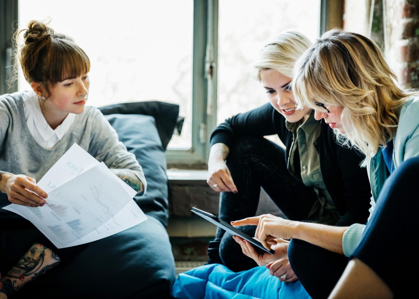 três mulheres empreendedoras a ver soluções para criar o seu próprio emprego
