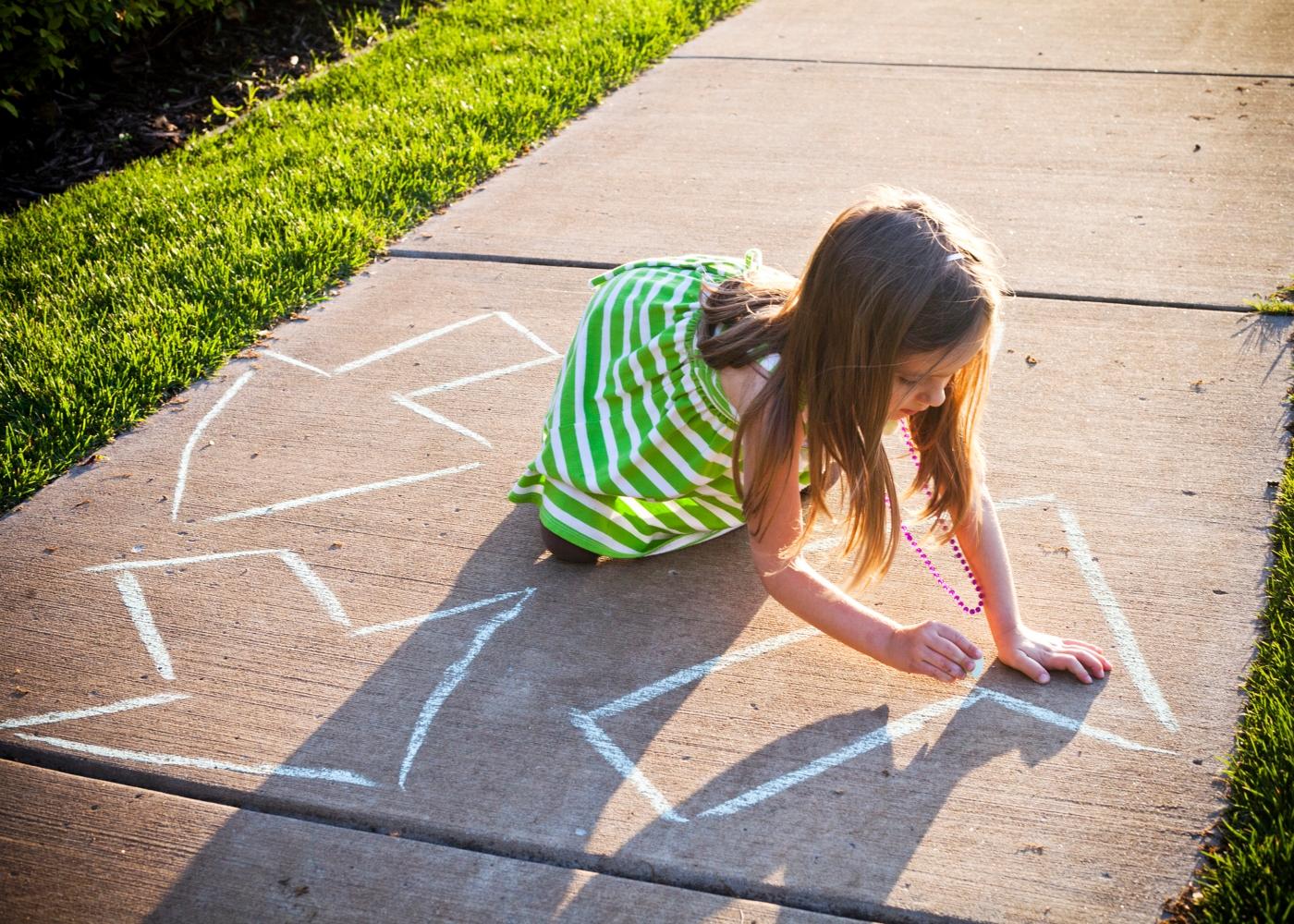 criança a desenhar símbolo da reciclagem no chão com giz