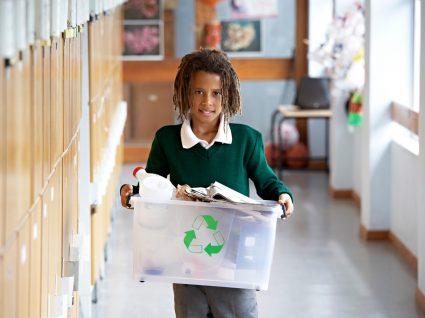 criança na escola a levar caixote com lixo para reciclar