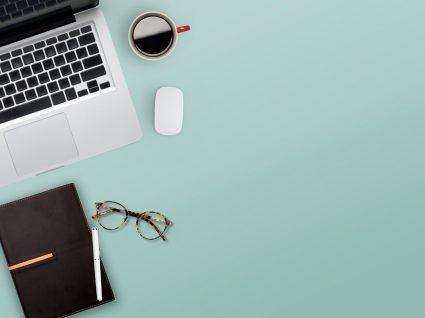 computador, caderno, óculos, rato e chávena de café dispostos em fundo neutro