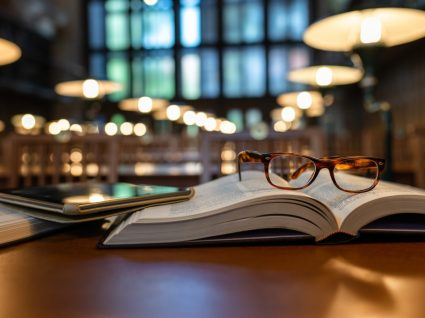 óculos pousados em cima de livro aberto numa biblioteca
