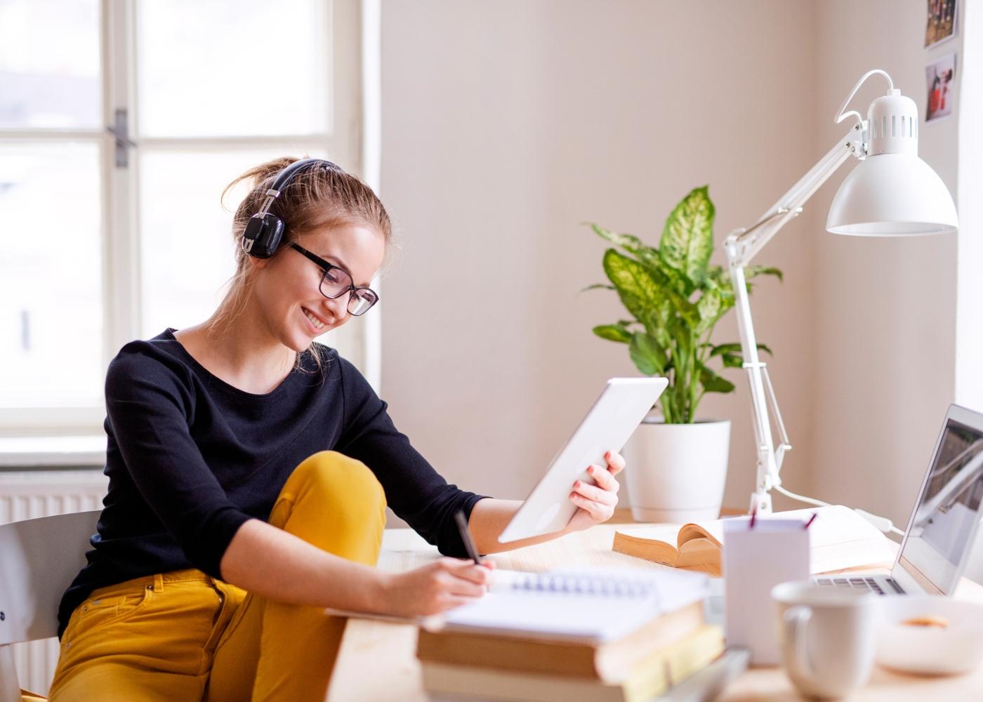 mulher a ler livro e tirar notas na secretária