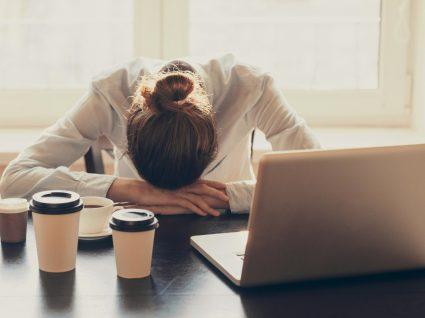 mulher com cabeça na secretária e vários copos de café espalhados pela mesa