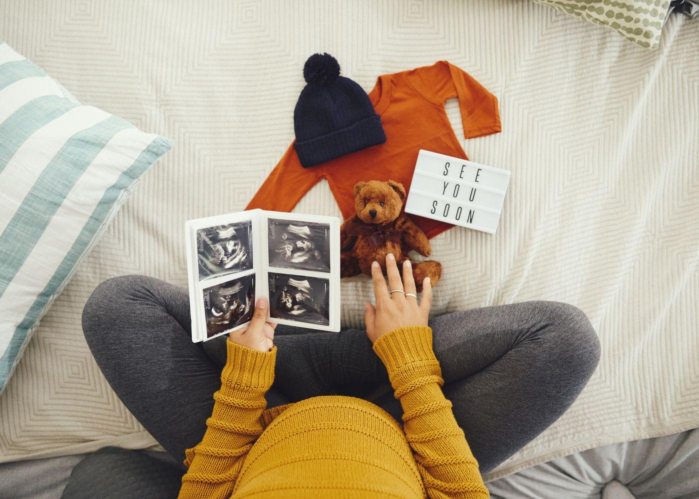 grávida com eco na mão e roupa de bebé pousada
