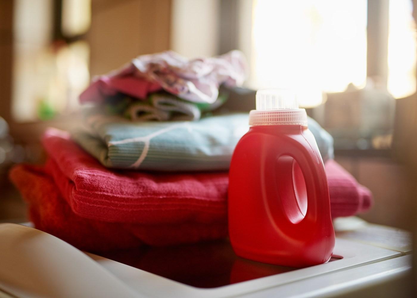 monte de roupa dobrada e detergente ao lado