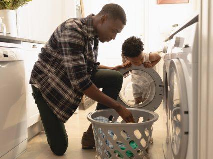 pai e filho a por a roupa na máquina para lavar