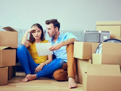 casal sentado no chão rodeado de caixas de mudança a olhar preocupado para um documento em papel