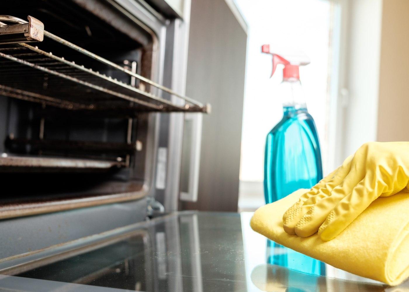 pessoa a limpar a gordura da cozinha e forno