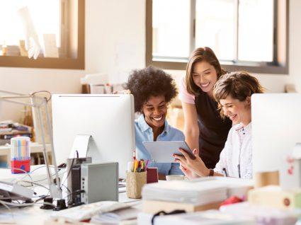três jovens felizes no trabalho