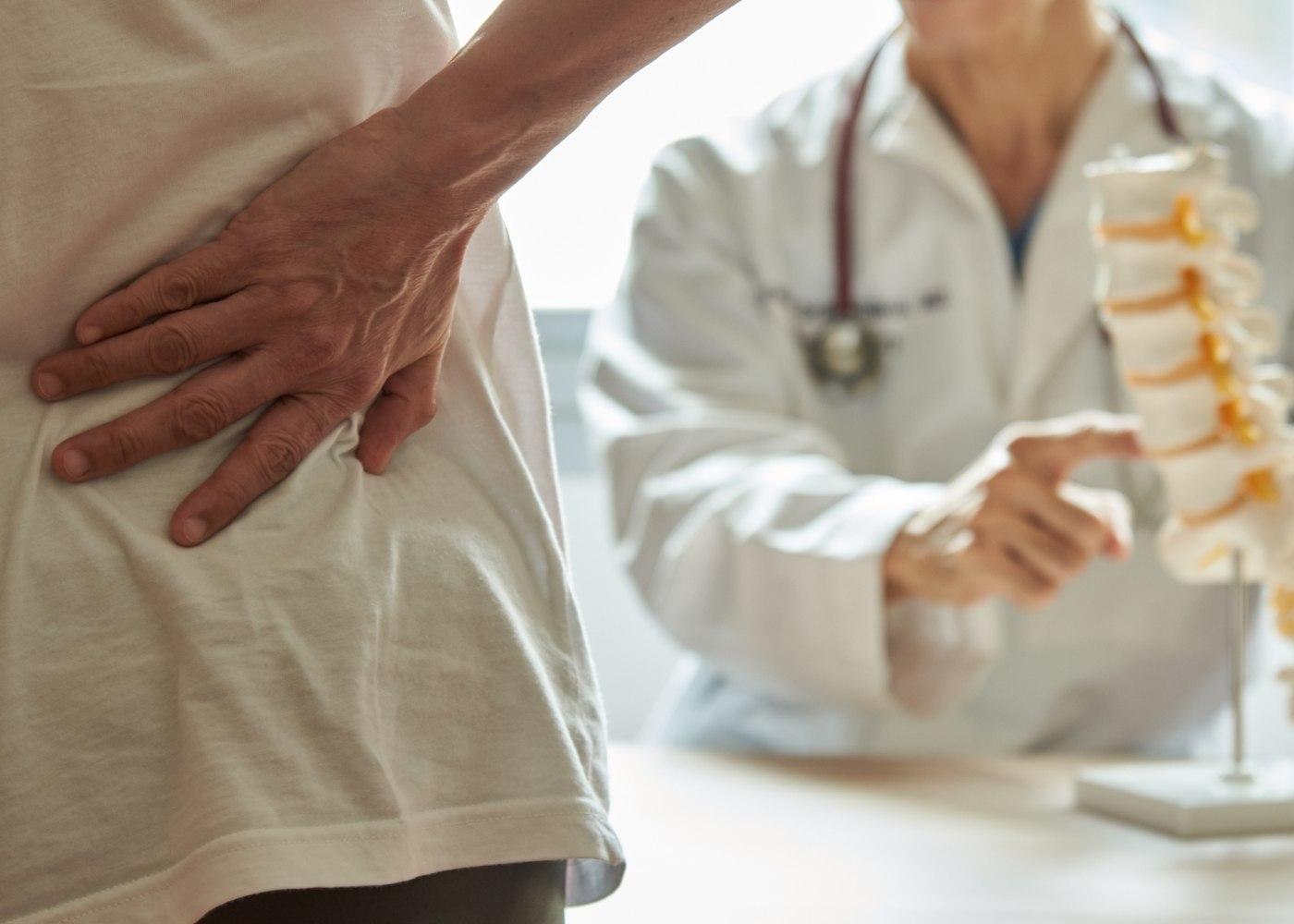 pessoa numa consulta médica com dores na coluna