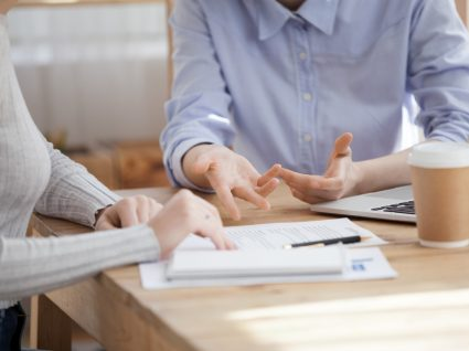 close up das mãos de duas pessoas a conversar sobre documentos na mesa