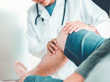 médico a examinar joelho de paciente