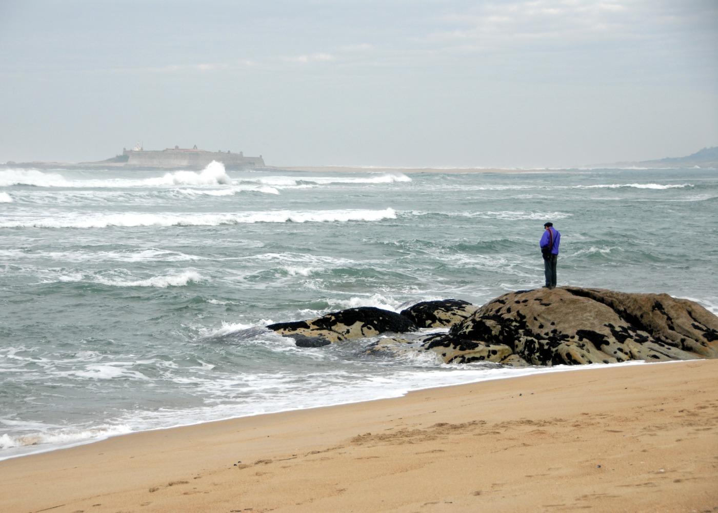 homem na praia de moledo