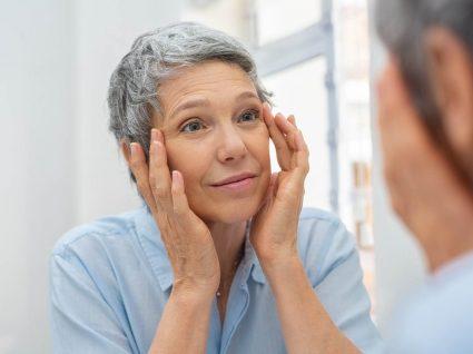 Mulher a aplicar maquilhagem para disfarçar as rugas