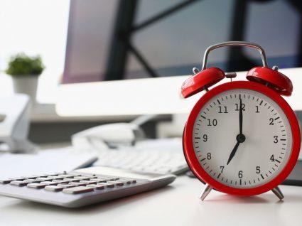 secretária com calculadora, relógio e computador a simbolizar redução do horário de trabalho