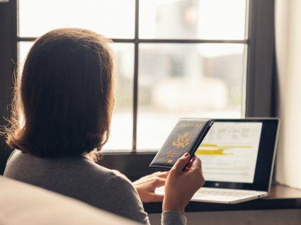 trabalhador estrangeiro ao computador com passaporte na mão