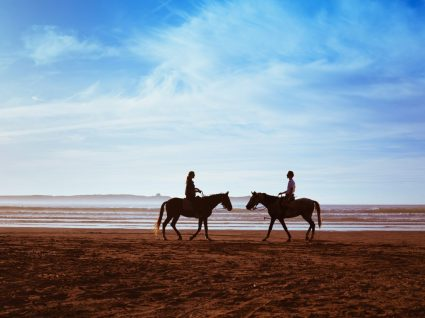Casal a andar a cavalo na praia