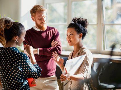 equipa a realizar uma dinâmica de grupo no trabalho