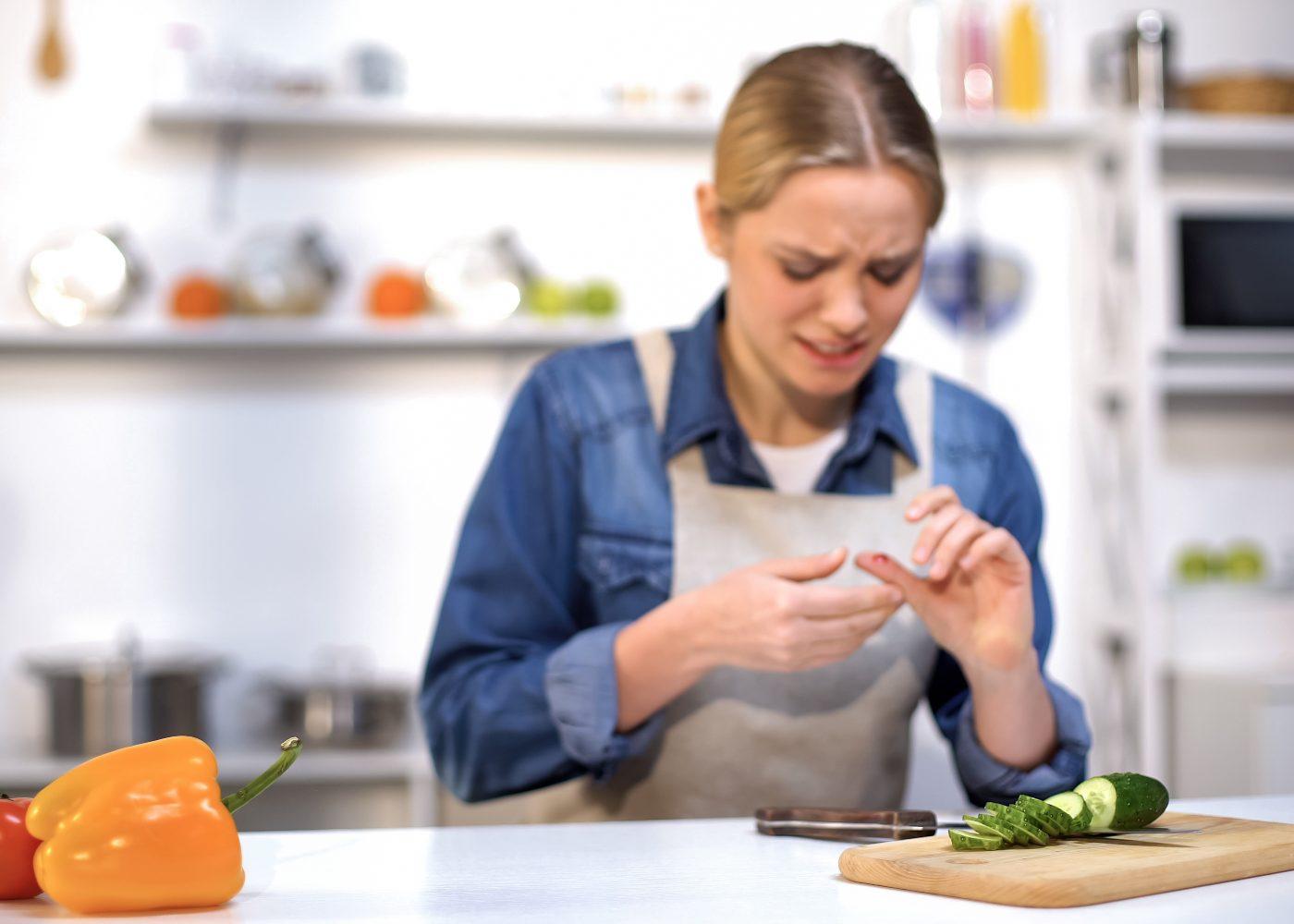 mulher com corte no dedo depois de cortar legumes