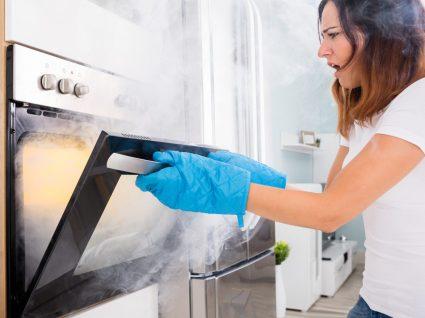 mulher com uma das emergências do dia dia mais comum: fumo a sair do forno