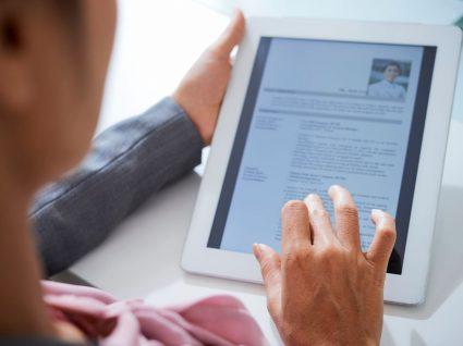 pessoa a ler um currículo num tablet