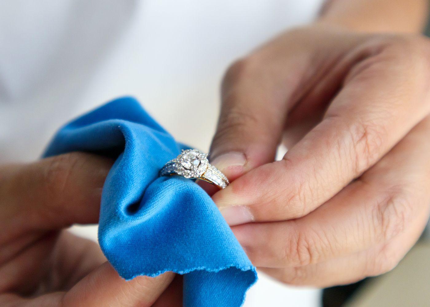 pessoa a limpar anel de prata com flanela
