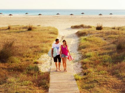 casal a caminhar na praia
