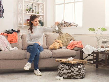mulher snetada no sofá a ver a desarrumação e roupa espalhada