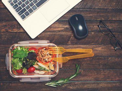 tupperware com comida ao lado de computador e rato pousados numa mesa