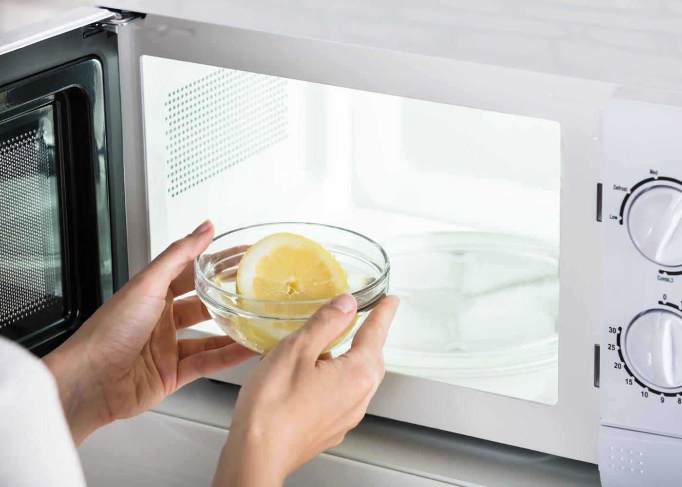 pessoa a colocar taça com água e limão dentro do microondas para limpar