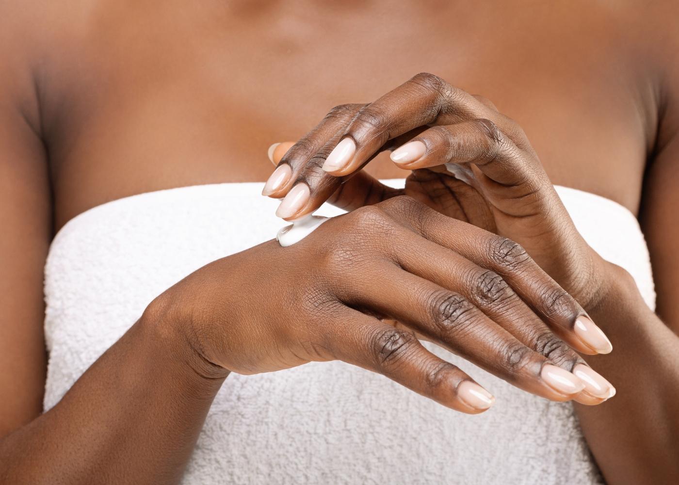 mulher a hidratar a pele das mãos