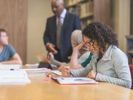 mulher em biblioteca a estudar para pós-graduação