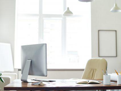 secretária em escritório com computador e papéis em cima