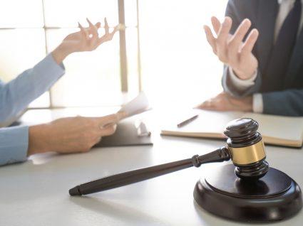duas pessoas a analisar documentos para denunciar a empresa