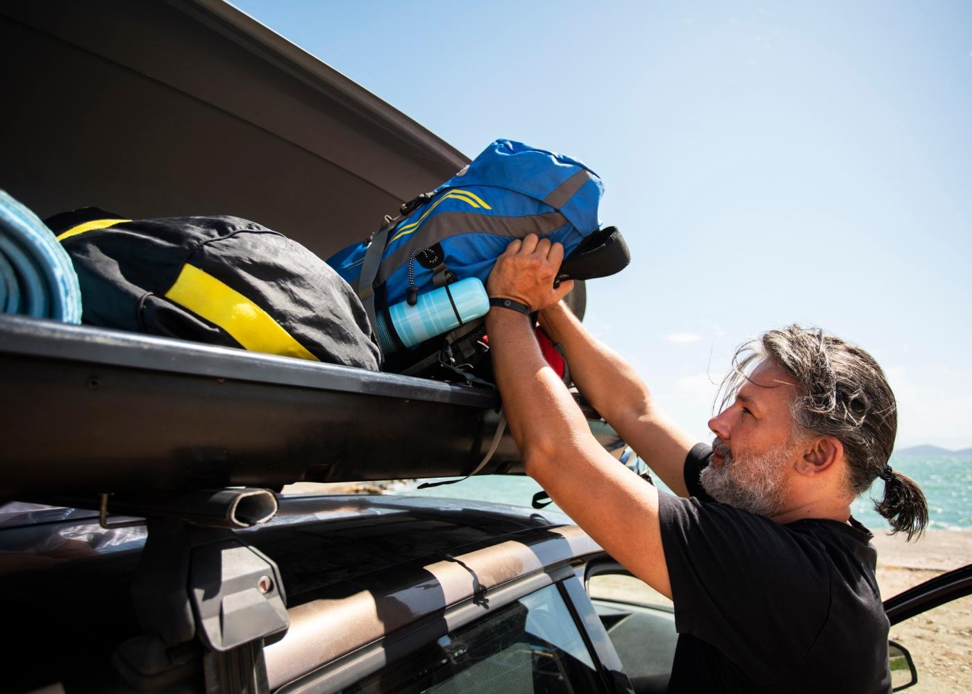 Homem a acomodar bagagem