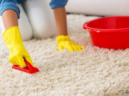 pessoa a esfregar carpete com escova