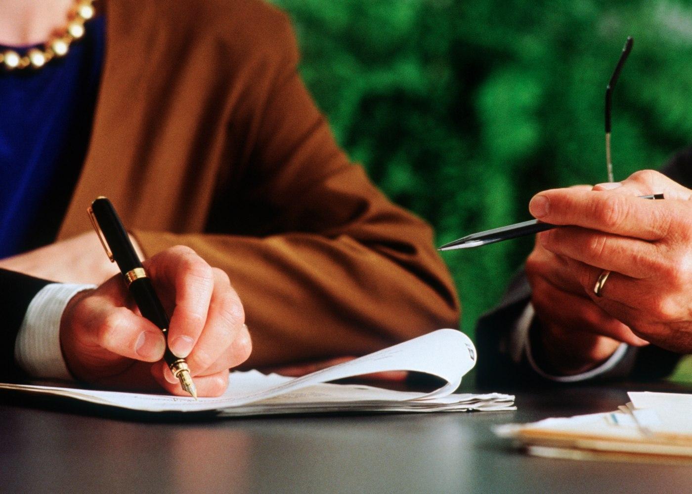 trabalhador e empregador a assinar papéis de layoff