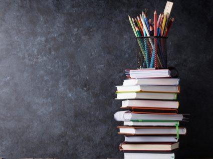 livros em cima uns dos outros com caixa de lápis no topo