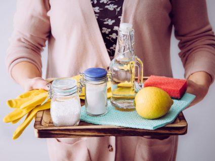 mulher a segurar tabuleiro com vinagre para limpeza e outros produtos