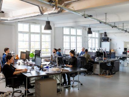 escritório open space com trabalhadores ao computador