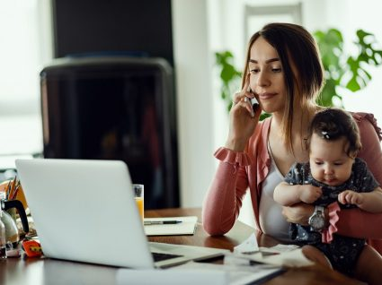 mãe a trabalhar com bebé ao colo e a informar-se sobre os direitos dos pais trabalhadores
