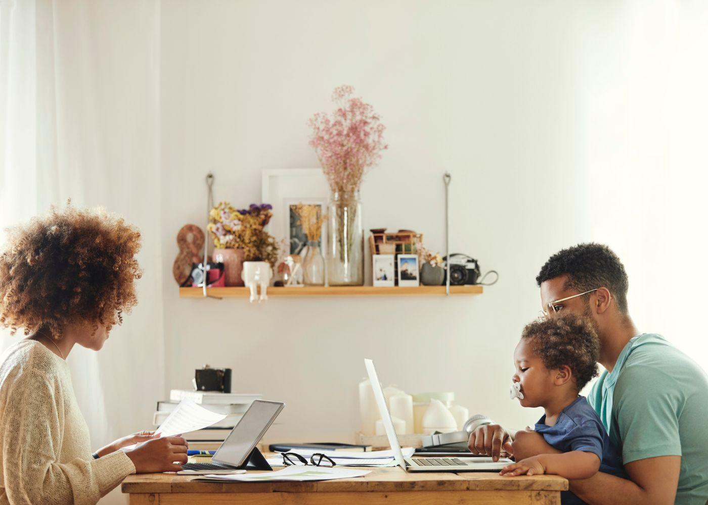 pais a trabalhar em casa com criança ao colo