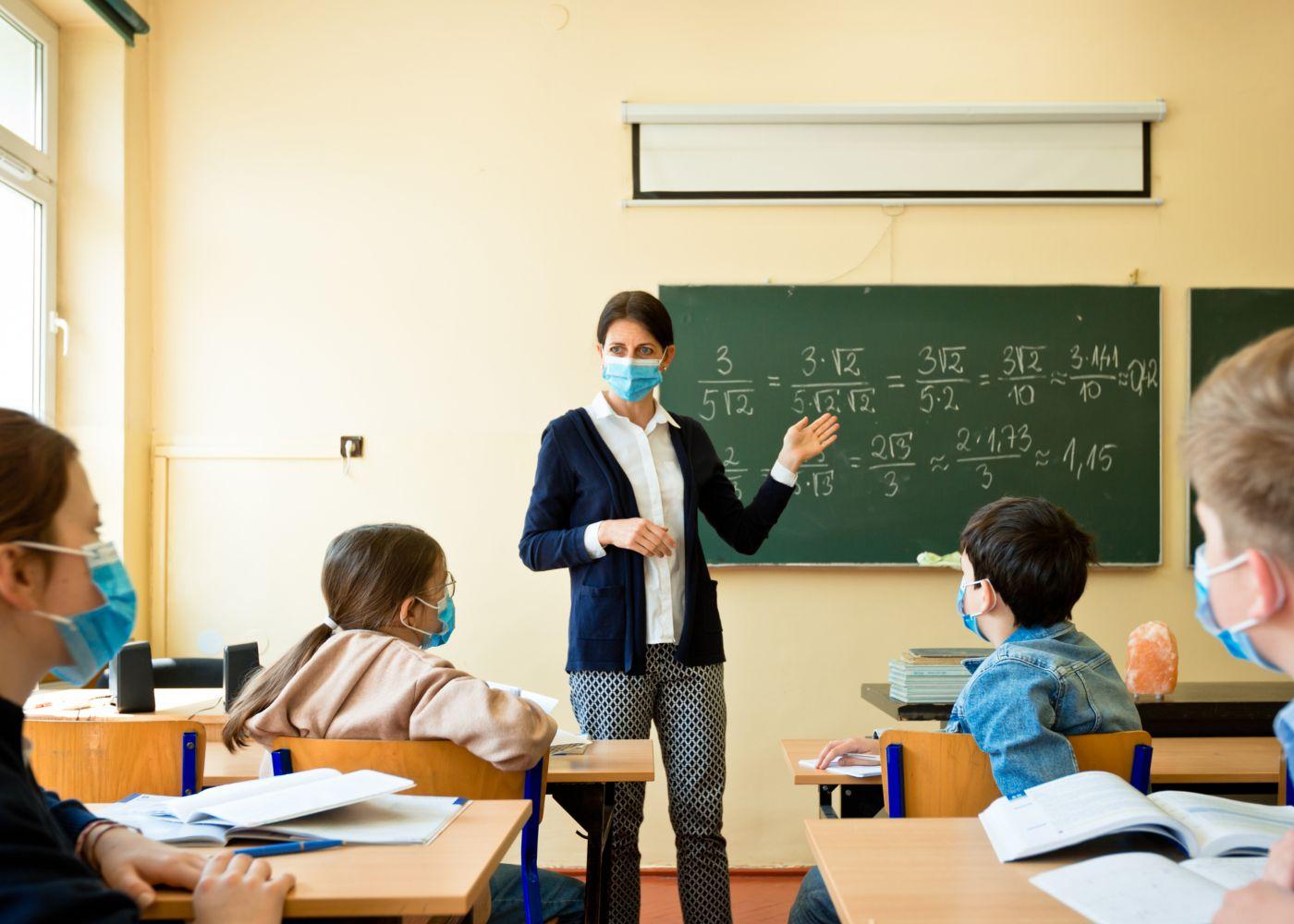 professora na sala com máscara a dar aulas e mostrar a importância dos professores
